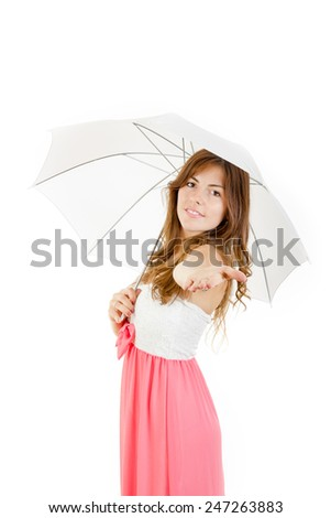 Charming young woman holding umbrella wearing elegant dress smiling with hand outstretched - stock photo
