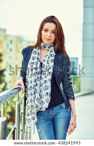 Charming young woman in a casual autumn clothes with stylish scarf. She looks into the camera and smiles. Outdoor. - stock photo