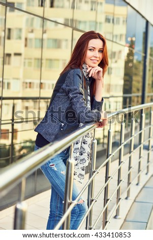 Charming young woman in blue jeans, black leather jacket and with stylish scarf, standing. Outdoors. - stock photo
