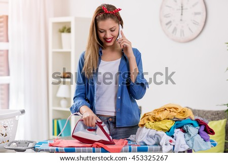 Charming young woman ironing laundry and talking on phone - stock photo