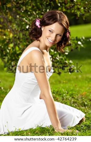 Charming young woman sits on a lown in a white dress in a summer garden - stock photo