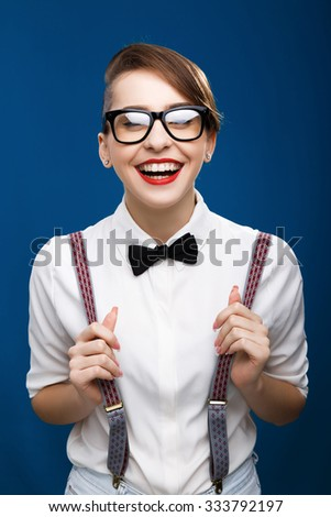 Charming young woman, wearing in white shirt, glasses, brace and black bow, is laughing on the blue background, in studio, waist up - stock photo