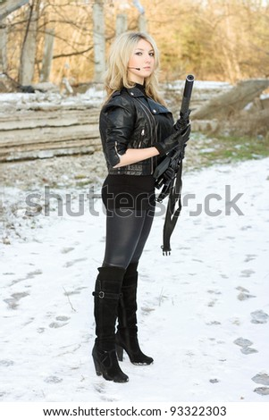 Charming young woman with a gun outdoors - stock photo