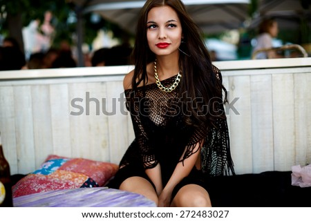 Charming young woman with brunette long hair sitting at beach cafe, seductive female in bikini enjoying perfect summer day outdoors, fashionable sexy girl relaxing during her summer holidays - stock photo