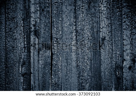 Charred black wooden wall. Abstract background with a burned boards textures closeup  - stock photo