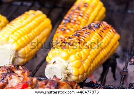 Charred corn on the cob cooking on a barbecue - stock photo