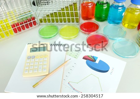 chart and experiment with Colorful fluid in petridish and bottle background on table in laboratory  - stock photo