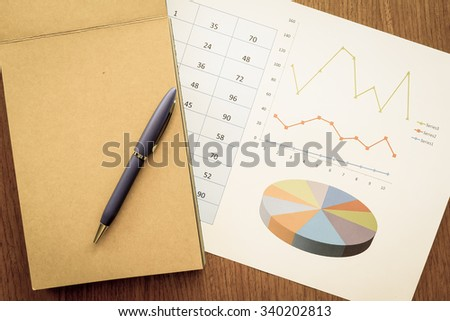 chart and note book on the wooden table with vintage color style - stock photo