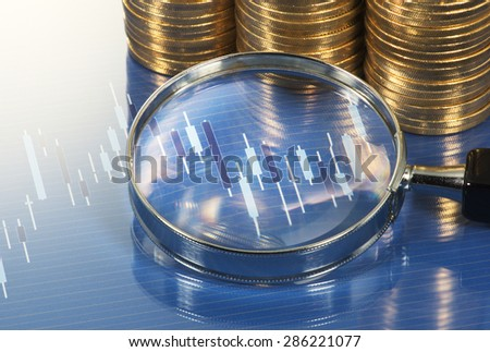 Chart, magnifying glass and pile of coins. Analyzing chart with magnifying glass. Market research study.  - stock photo