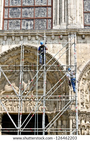 CHARTRES - MAY 19: Workers restore exterior of the medieval Cathedral on May 19, 2010 in Chartres, France. The  cathedral is included in UNESCO world heritage list. - stock photo