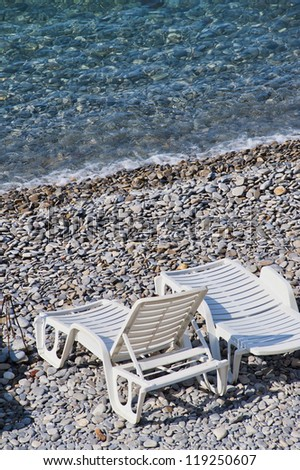 chase lounge on the rocky beach at Nice France - stock photo