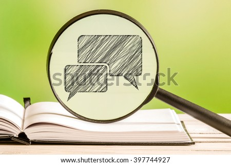 Chat information with a pencil drawing of a talk bubble in a magnifying glass - stock photo