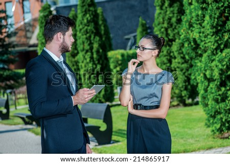 Chat with a colleague. Smiling businessman and successful businesswoman in formal clothes standing on the street and discuss business matters. Young businessman holding a tablet in his hands - stock photo