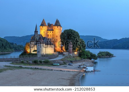 Chateau de Val in Auvergne, France at twilight overlooking the artificial lake surrounding it. - stock photo