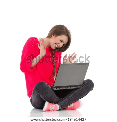 Chatting online. Smiling young woman waving hands and looking at computer screen. Full length studio shot isolated on white. - stock photo