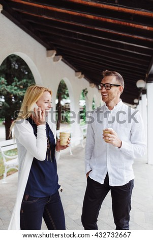 Chatting with colleagues over some coffee.  Young woman standing with her friend and talking on cellphone while having a coffee break. - stock photo