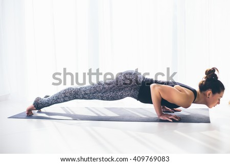 Chaturanga dandasana. Beautiful yoga woman practice in a training hall background. Yoga concept. - stock photo