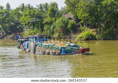 CHAU DOC, VIETNAM - JANUARY 2, 2013: Rural life in Mekong delta- Barge transports rice on Bassac River  - stock photo
