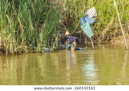CHAU DOC, VIETNAM - JANUARY 2, 2013: Rural life in Mekong delta- Local woman washes clothes in Bassac River  - stock photo