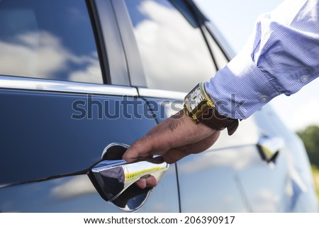 Chauffeur's hand opening passenger door on limousine - stock photo