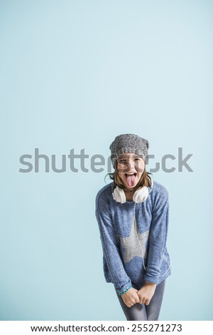 Cheaky girl sticking tongue out - stock photo