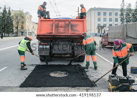 Cheboksary, Russia, May 1, 2016: Repair road construction, asphalting people in the city center. - stock photo