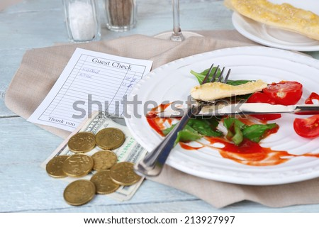 Check and remnants of salad on table in restaurant  - stock photo