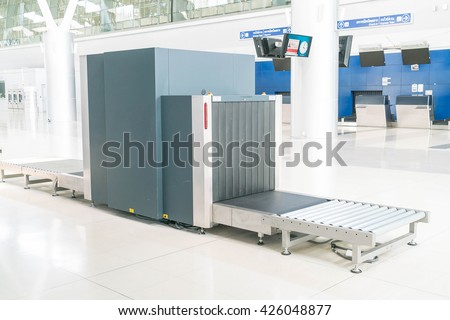 Check baggage at the airport x-ray scanner - stock photo