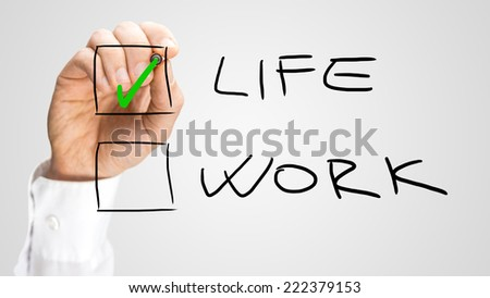 Check Box with Life and Work Choices. One Hand Checking Life Option. Isolated on Gray Background. - stock photo