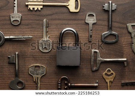 check-lock and different keys on wooden background concept - stock photo