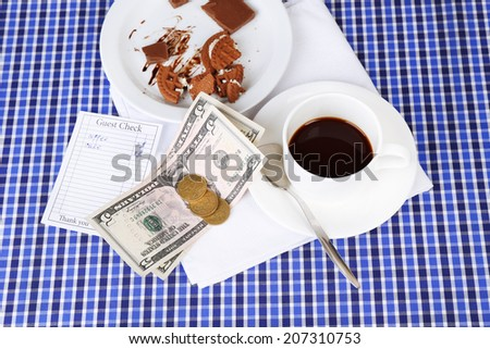 Check, money and remnants of food and drink on table close-up - stock photo