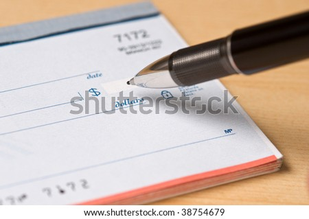 Checkbook with a fancy pen writing in a dollar amount on the check, sitting on a light wood desktop. - stock photo