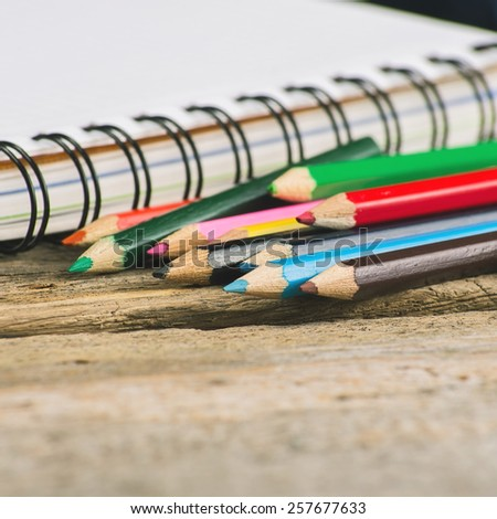 Checked blank notebook with multicolored pencils on wood background - stock photo