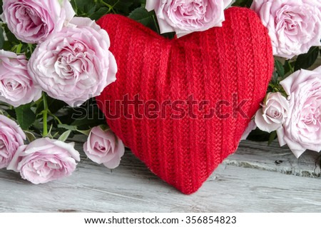 Checked handmade heart against of red and pink roses on wooden table. - stock photo