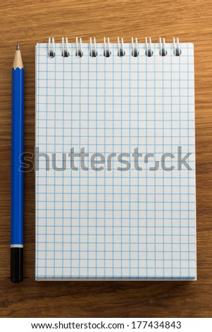 checked notebook on wood background - stock photo