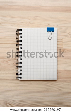 Checked notebook with blue binder clip on wooden background. - stock photo