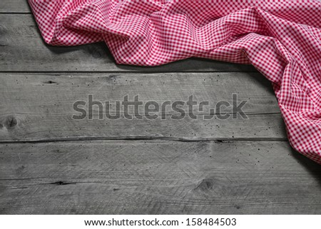 Checkered fabric as border on grey wooden background for christmas, birthday, publicity, mother's day, valentine's day or a advertising, board - stock photo