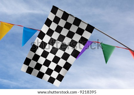 Checkered flag against colorful penants and a blue sky - stock photo