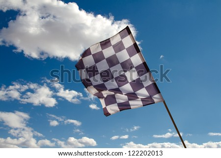 Checkered flag against the blue sky with clouds - stock photo