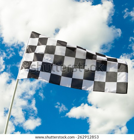 Checkered flag waving in the wind with clouds on background - outdoors shoot - stock photo