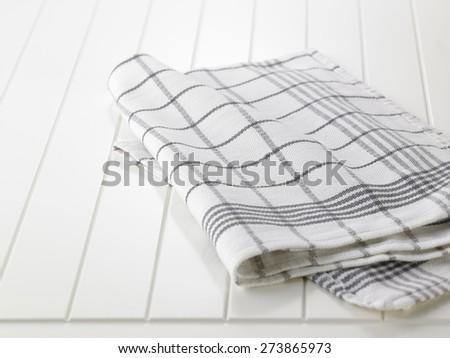 checkered napkin on wooden white  table - stock photo
