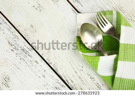 Checkered napkin with fork and spoon on wooden table background - stock photo