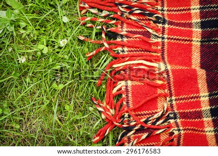 Checkered plaid for picnic on green grass. Picnic background - stock photo