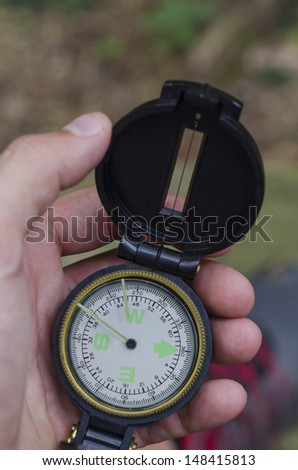 Checking a compass on a hike to stay on trail. - stock photo
