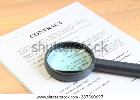 checking a contract with a mgnifier - stock photo