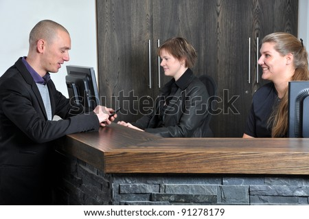 Checking an appointment at the receptions desk - stock photo
