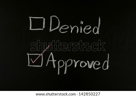 checking approved written on blackboard - stock photo