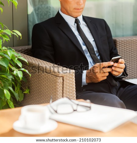 Checking business messages. Confident mature man in formalwear typing message on his mobile phone and while sitting at the chair outdoors with coffee cup on foreground - stock photo