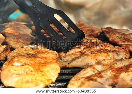 Checking for the right amount of chicken breast with a big fork - stock photo