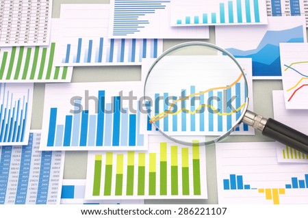 Checking graphs. Searching key data and analyzing. Many graphs and magnifying glass.  - stock photo